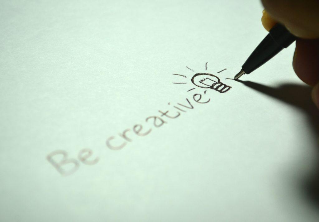 Kreativität fördern: Mit einem Stift wird be creative geschrieben und eine Glühbirne gezeichnet.