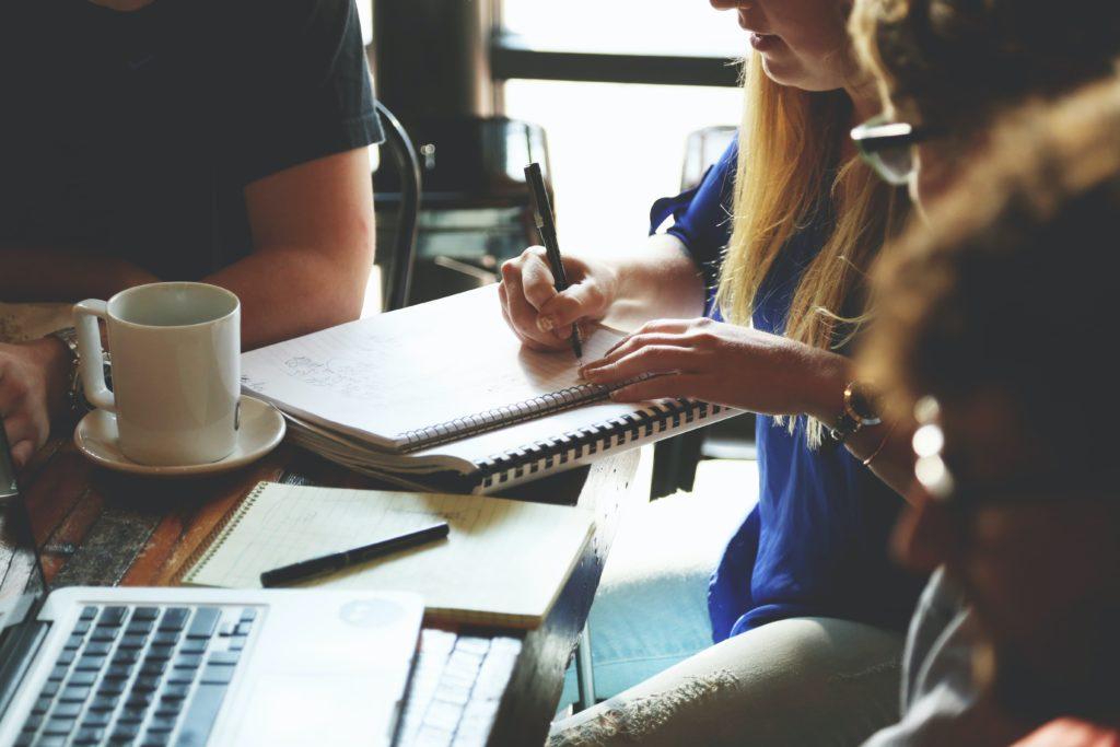Illustration Mitarbeiergespräche: Eine Frau macht sich Notizen an einem Tisch mit mehreren Personen.  Mitarbeitergespräche fördern das Verständnis für die Mitarbeitenden.